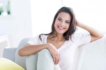 Smiling beautiful brunette relaxing on the couch
