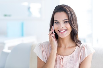Smiling beautiful brunette speaking on the phone