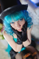 Portrait of beautiful girl with blue curly hair and hat