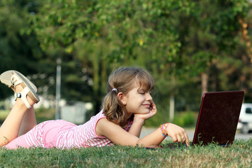 happy little girl lying on grass with laptop