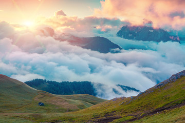 Colorful summer sunrise in the foggy Val di Fassa valley
