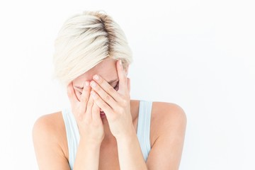 Sad blonde woman crying with head on hands