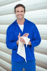 Composite image of confident mechanic wiping hand with napkin