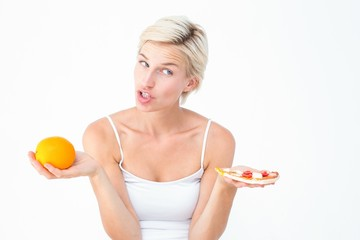 Pretty woman deciding between pizza and an orange