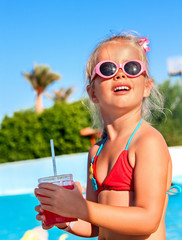 Child drinking  near swimming pool.