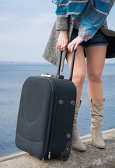 Legs of a woman in a boots and with a suitcase in front of the s