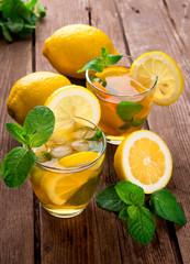 Lemonade with fresh lemon and mint on wooden background