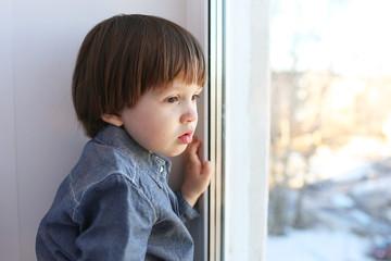 Sad little boy looks out of window