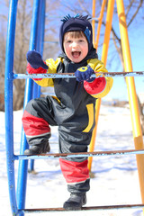 Happy smiling child in overall plays on climber in winter