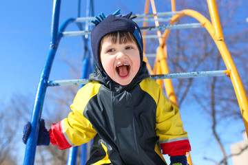 Happy smiling child in overall on climber in winter