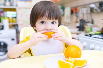 Little child eats orange
