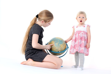 adorable little two sisters 9 year and  1  year old with globe