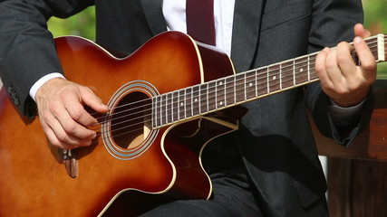light haired bearded man in suit plays guitar in different frets