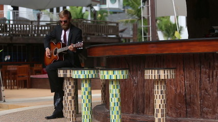 bearded man in suit and glasses plays guitar sitting on bar