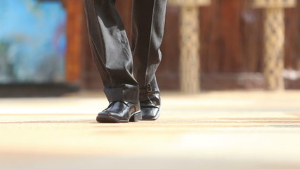 man in black trousers and shoes steps to point of focus and back