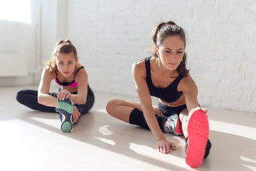 Group of fit women working stretching leg muscles back to warm