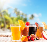 Fresh juice with fruits on wooden table, tropical beach