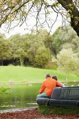 Mature couple sitting on bench in park