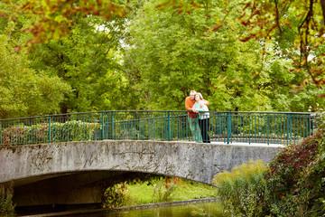 Retired couple hugging on bridge