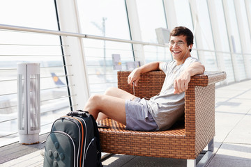 Smiling man waiting for flight at airport