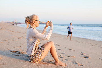 Woman taking photo on beach