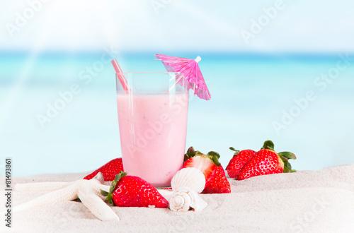 Leinwandbild Motiv Strawberry milk shake on sand with tropical beach