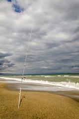 Angel im Sand bei Gewitter am Strand