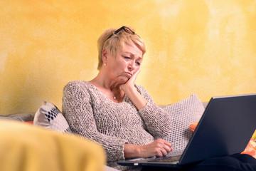 Attraktive Frau schaut besorgt auf Ihr Laptop