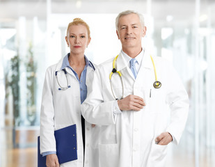 Female doctor and male professor standing at clinic