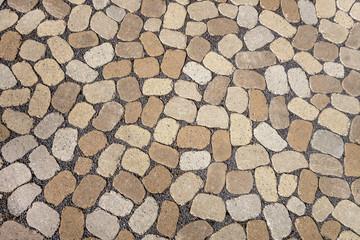 Mosaik aus ovalen grauen und braunen Pflastersteinen