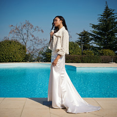Young beautiful bride intimate outdoors close to swimming pool.