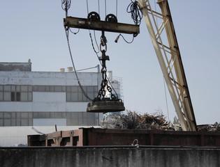 Magnetic crane loads scrap metal at the dump