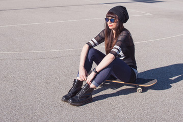 Young woman with skateboard outdoors in a basketball playground.