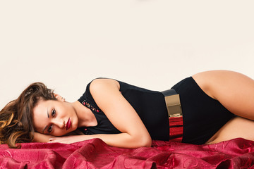 Fashion woman portrait laying down on the floor on dark red fabr