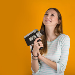 Laughing woman with vintage film camera close up against orange