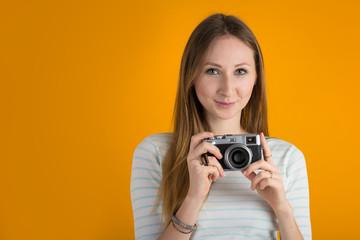 Smiling woman with vintage camera close up against orange backgr