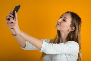 Young woman taking a selfie with mobile phone against orange bac