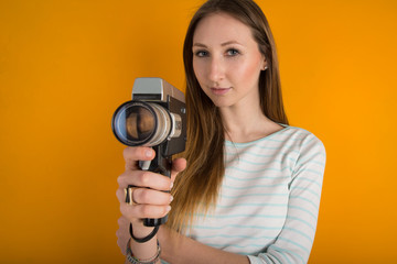 Woman with vintage film camera close up against orange backgroun