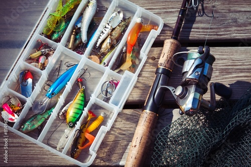 Foto op Canvas Vissen Fishing Lures in tackle boxes with spinning rod and net