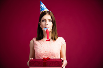 Woman blowing in whistle and holding gift box