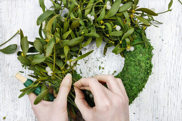 Florist at work: woman making mistletoe wreath