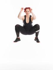 Rothaarige Frau im Fitnessstudio geht in die Hocke