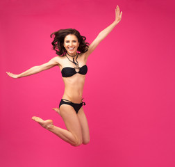 Happy woman jumping in bikini