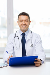 happy doctor with clipboard in office
