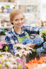 happy woman taking care of flowers in greenhouse