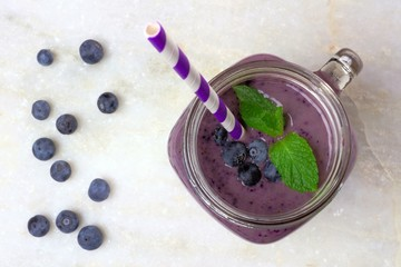 Blueberry smoothie with mint in mason jar glass on white marble
