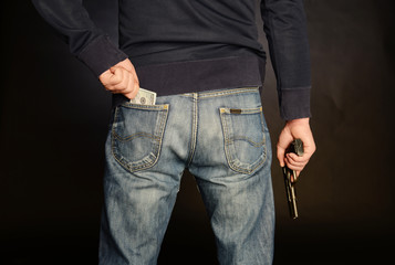 A man with a gun is getting money from his pocket.