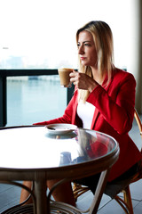 Young attractive businesswoman enjoying her coffee break in cafe