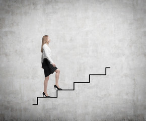 Young business woman is going up to the stairs.
