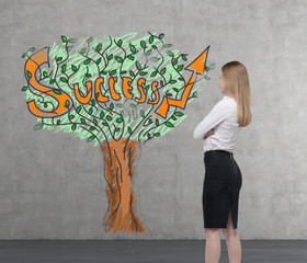 Young business woman is looking on a wall with success tree.
